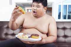 Overweight person eating donuts Stock Photos