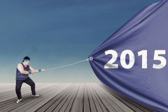Overweight person pulling number 2015 Stock Photos