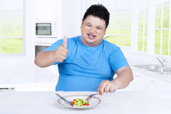 Overweight person with salad and OK sign Stock Image