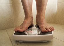 Overweight person on scale. Overweight person standing on bathroom scale Stock Photo