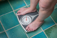 Overweight person. A severely overweight person weighing herself or himself on a bathroom scale royalty free stock image