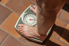 Overweight person. A severely overweight person weighing herself or himself on a bathroom scale Stock Photos