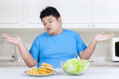 Overweight person with two kinds of food 2 Royalty Free Stock Photography