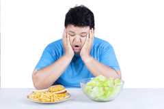Overweight person with two kinds of food Stock Image