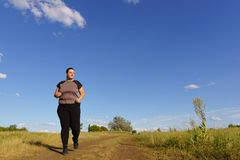 Overweight runner go jogging outdoors. Weight loss royalty free stock image