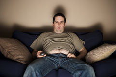Overweight slob watching TV stock images