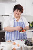 Overweight and smiling woman making breakfast. Stock Images