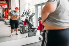 Overweight sweaty woman against mirror in gym Stock Photography