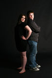 Overweight teenage couple standing back to Stock Image