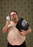 Overweight white male holding scales while looking at milkshake. Overweight white male is holding scales after a workout and looking at a milkshake while stock photography