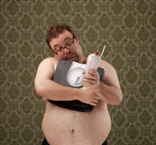 Overweight white male holding scales while resisting temptation. An overweight white male, just finishing his workout, hugs the scales while looking at a stock images