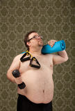 Overweight white male after successful workout. A shirtless overweight white male holding weights, bands and mat looks up and reflects on his workout Stock Image