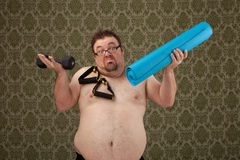 Overweight white male wonders how to use equipment. A shirtless, overweight white male holding weights, bands and mat looking confused and wondering what to do Royalty Free Stock Photos