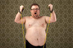 Overweight white male working out with bands. A shirtless overweight white male struggles with weight bands during a workout stock photos