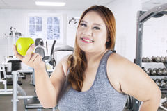 Overweight woman and apple in gym center Stock Photography