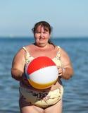 Overweight woman with ball on beach. Near sea Stock Photos