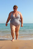 Overweight woman on beach. Overweight woman walking on beach near sea royalty free stock photos