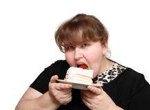 Overweight woman biting cake stock photos
