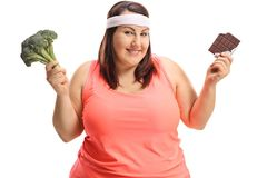 Overweight woman with broccoli and chocolate Stock Photos