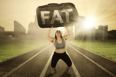 Overweight woman with burden on track Stock Images