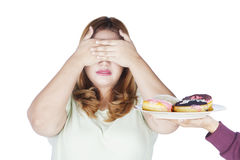 Overweight woman closed eyes for donuts. Portrait of overweight woman closed her eyes for a plate of donuts, isolated on white background Royalty Free Stock Image