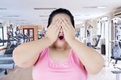 Overweight woman closing eyes in fitness center. Portrait of overweight woman looks worried while closing eyes with her hands in the fitness center stock photography