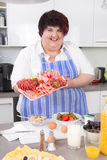 Overweight woman cooking and posing in the kitchen with a plate Stock Photos