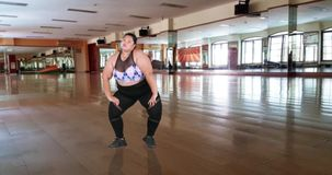 Overweight woman dancing in dance hall. Overweight young woman dancing in the dance hall while wearing sportswear, shot in 4k resolution stock video footage