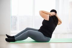 Overweight woman doing crunches on mat at home. Weight loss, fitness, sport, exercising, home workout, training and lifestyle. young plus size woman doing royalty free stock image