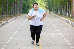 Overweight woman doing runs exercise on the road. Portrait of overweight woman wearing sportswear while doing runs exercise on the road stock image