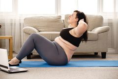 Overweight woman doing sit-ups on mat at home. Fitness, sport, weight loss, exercising, home workout, training, lifestyle. young plus size woman doing sit-ups on royalty free stock images