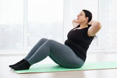 Overweight woman doing sit-ups on mat at home. Fitness, sport, weight loss, exercising, home workout, training, lifestyle. young plus size woman doing sit-ups on stock photo