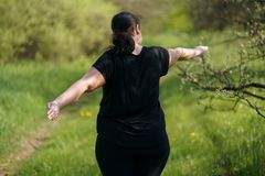Overweight woman doing yoga in morning park royalty free stock photo
