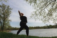 Overweight woman doing yoga, relaxing near lake stock images