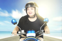 Overweight woman driving a motorcycle Royalty Free Stock Photos
