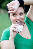 Overweight woman eating a chocolate Stock Image