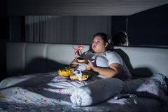 Overweight woman eating junk food in bed before sleeping stock image