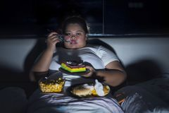 Overweight woman eating junk food in bed before sleeping. Unhealthy lifestyle concept: Overweight woman eating junk food in bed before sleeping stock photo