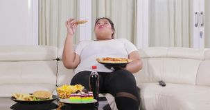 Overweight woman eating pizza on sofa