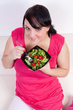 Overweight woman eating a salad Stock Image