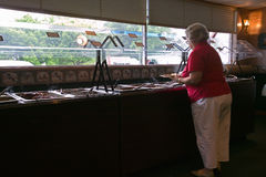 Overweight woman eats at buffet Royalty Free Stock Images