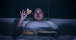 Overweight woman eats pizza at night on bed