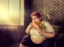 Overweight woman eats sandwich, bulimic stock image