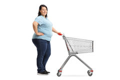 Overweight woman with an empty shopping cart waiting in line. Full length portrait of an overweight woman with an empty shopping cart waiting in line isolated on Stock Images