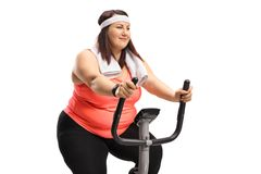 Overweight woman on an exercise bike. Isolated on white background Royalty Free Stock Photo