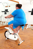 Overweight woman exercising on bike Royalty Free Stock Photo