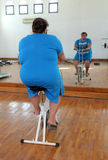 Overweight woman exercising on bike Stock Photography