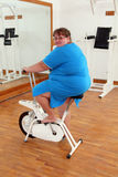 Overweight woman exercising on bike Stock Photos