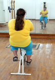 Overweight woman exercising on bike simulator Royalty Free Stock Images