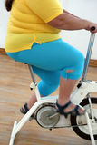 Overweight woman exercising on bike simulator Stock Image